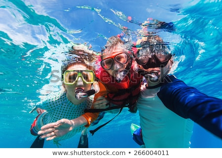 Underwater portrait of family snorkeling together at clear tropical ocean Stock photo © galitskaya