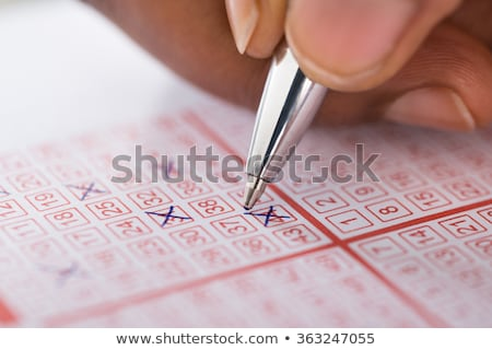 Stock photo: Person Marking Number On Lottery Ticket With Pen