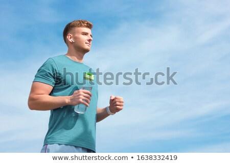 Fiatal sportoló drótnélküli fülhallgató áll kint Stock fotó © deandrobot