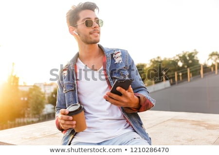 Handsome young guy walking outdoors using mobile phone drinking coffee listening music. Stock photo © deandrobot