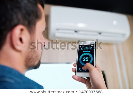 Stock photo: Young man using smart application to adjust temperature of air conditioner