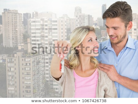 Couple  Holding key in front of high rise apartments Stock photo © wavebreak_media