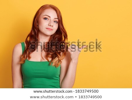 Indoor shot of satisfied red haired woman in black clothing and white sneakers, shows slender legs,  Stock photo © vkstudio