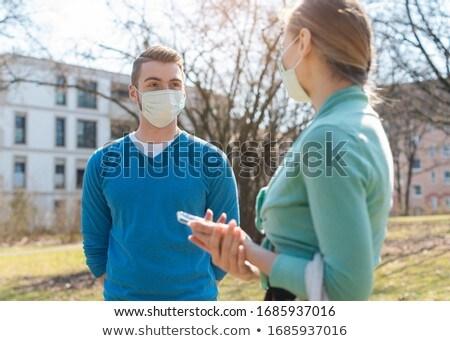 Couple flirting in the park despite Covid-19 wearing masks Stock photo © Kzenon