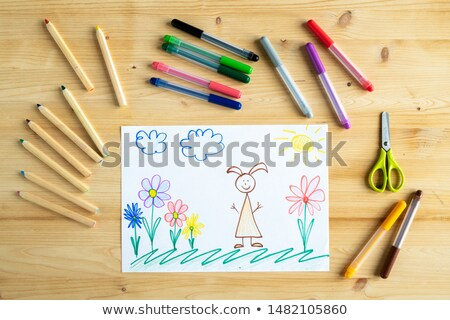 Drawing of child or schoolkid of elementary school lying on wooden table Stock photo © pressmaster