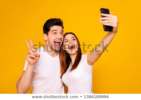 Happy young friends hugging and taking selfie Stock photo © cienpies