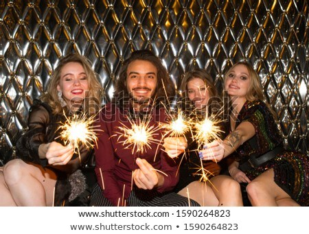 Happy girls and guy with sparkling bengal lights sitting by wall in night club Stock photo © pressmaster