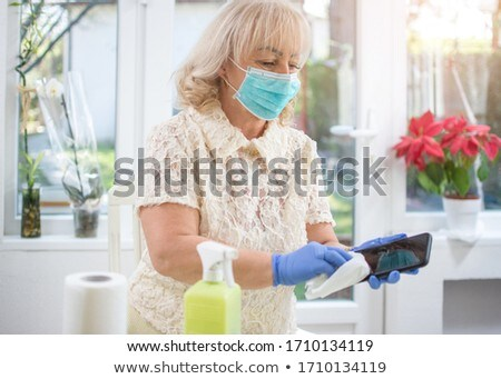 disinfection of the phone. A woman in a medical mask holds a telephone and a spray disinfector in he Stock photo © galitskaya