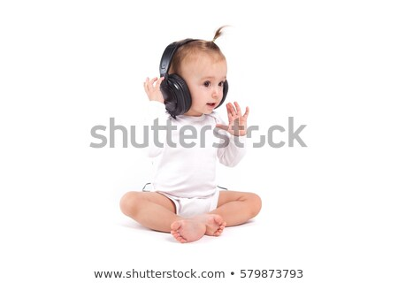 pretty cute little girl in white pijamas with headphones on head Stock photo © Traimak
