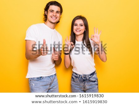 Happy cute young woman posing isolated over yellow background using mobile phone. Stock photo © deandrobot