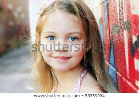Little girl in an urban setting smiles at the camera Stock photo © Lopolo