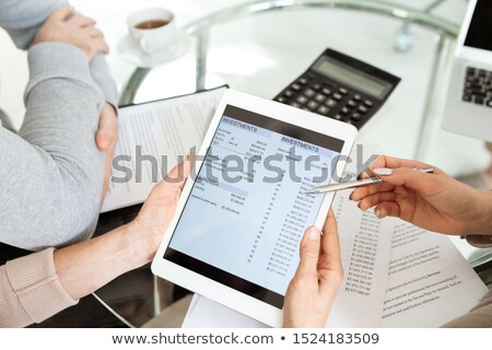 Group of humans discussing electronic financial document on tablet display Stock photo © pressmaster