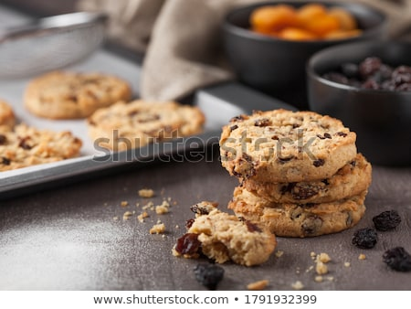 Homemade organic oatmeal cookies with raisins and apricots and bottle of milk on dark wooden backgro Stock photo © DenisMArt