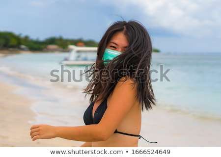 Enjoying vacation in China. Young woman in medical mask with national chinese flag in Forbidden City Stock photo © galitskaya