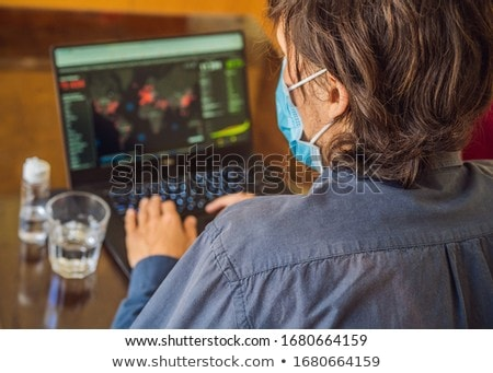 Coronavirus. A man looks at a map of the coronovirus. Working from home wearing protective mask. qua Stock photo © galitskaya