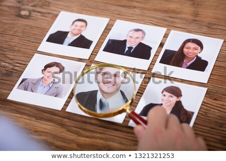 Stok fotoğraf: Businessperson Looking At Candidates Photograph