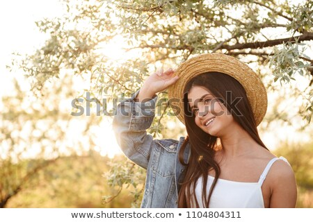 Photo of caucasian cheerful girl in straw hat with long dark hai Stock photo © deandrobot