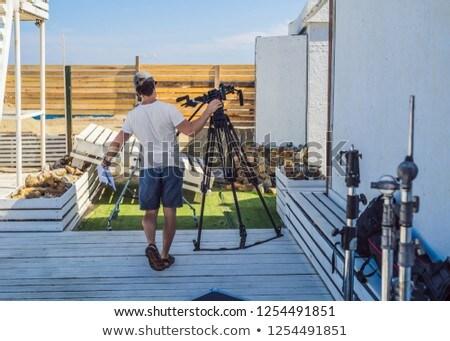 assistant on cinema shoot prepares filmmaking gear Stock photo © galitskaya