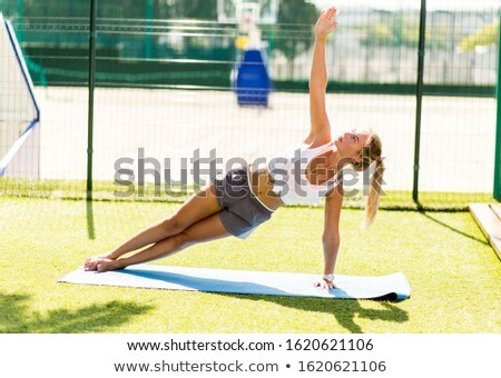 Young woman exercising workout fitness doing planking outside on Stock photo © Freedomz