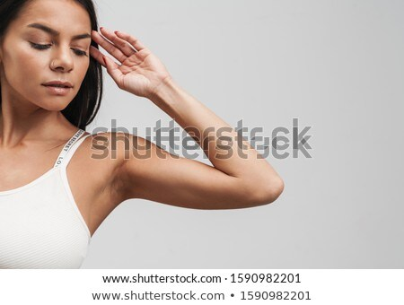 Cropped image of fitness brunette woman in sportswear looking do Stock photo © deandrobot