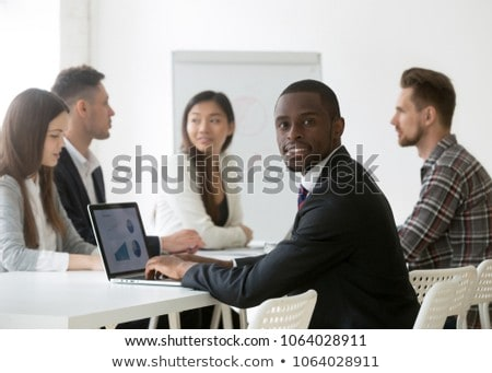 Portrait of handsome mixed race male executive using laptop in modern office with diverse colleagues Stock photo © wavebreak_media