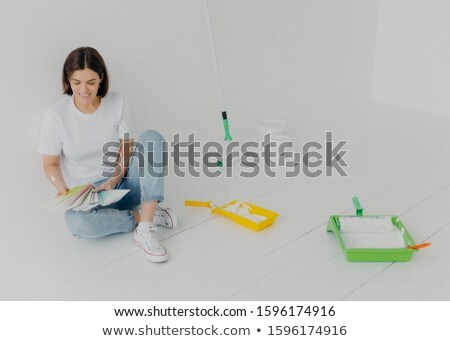 Satisfied brunette woman chooses color from samples, going to refurbish room, sits on floor in casua Stock photo © vkstudio
