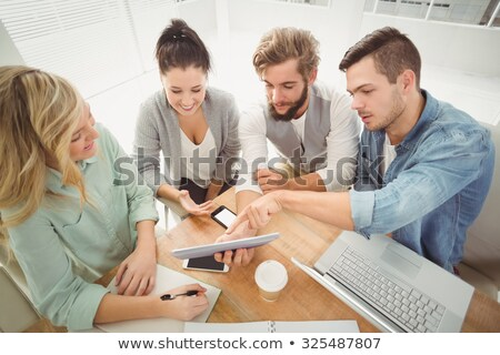High angle view of woman using mobile phone while working on laptop in living room at home Stock photo © wavebreak_media
