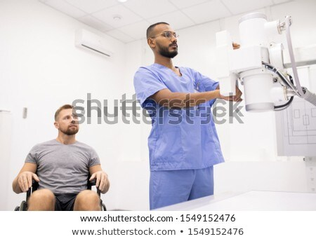young sportsman on wheelchair looking at doctor testing new medical equipment stock photo © pressmaster