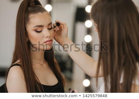Make-up artist styling a model in her studio Stock photo © Kzenon