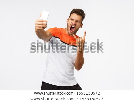 Gym rocks. Enthusiastic, handsome muscular young man in sports t-shirt shouting satisfied, making co Stock photo © benzoix