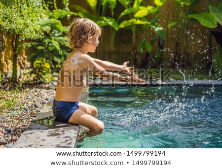 Happy boy with sun painted by sun cream on shoulder playing by the pool. Summer vacation concept. Sp Stock photo © galitskaya