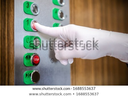 Pressing elevator button with hand wearing medical glove for hygiene, touching public surface, perso Stock photo © Maridav