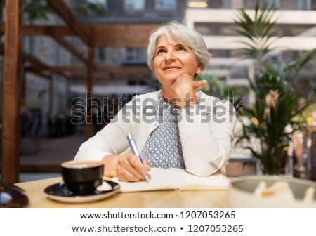 senior woman with notebook dreaming at street cafe stock photo © dolgachov