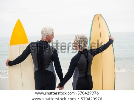 Rear view of senior couple standing with surfboard on the beach Stock photo © wavebreak_media