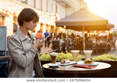 Female millennial with smartphone taking photo of dessert and drink in cafe Stock photo © pressmaster