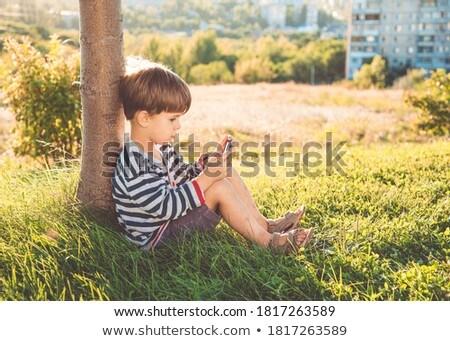 Nino jugando teléfono sesión hierba verde moderna Foto stock © galitskaya