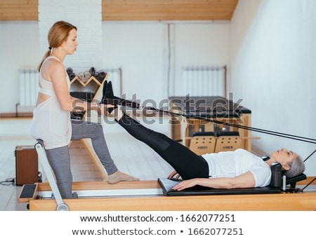 Stock photo: Woman performing stretching exercise with the help of trainer