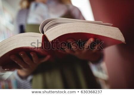 Mid-section of schoolgirl reading book in library Stock photo © wavebreak_media
