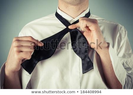 portrait of handsome young man wearing an undone black tuxedo stock photo © feedough