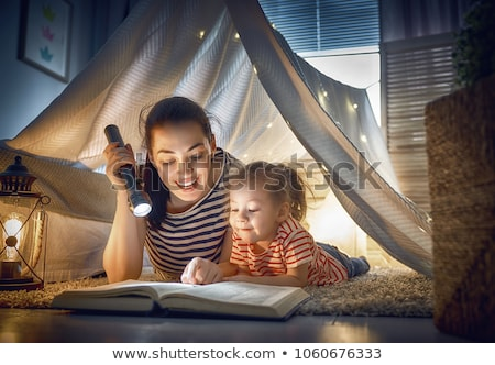 happy girls reading book in kids tent at home Stock photo © dolgachov