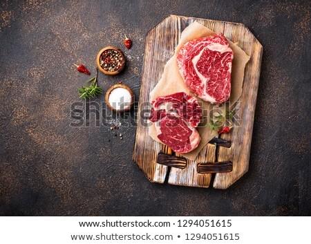 Raw marbled ribeye steak and butchers knife Stock photo © furmanphoto