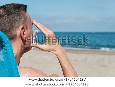 man putting on or taking off a mask on the beach Stock photo © nito