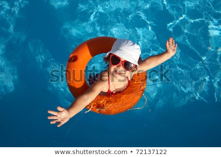 Little girl in sunglasses relaxing in swimming pool, enjoying suntans, swims on inflatable yellow ma Stock photo © Illia