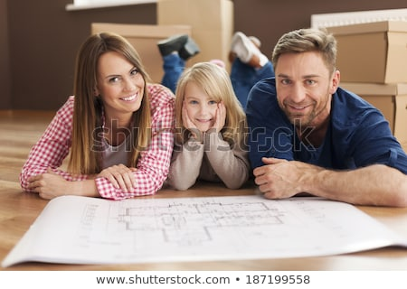 man with blueprint and boxes moving to new home stock photo © dolgachov