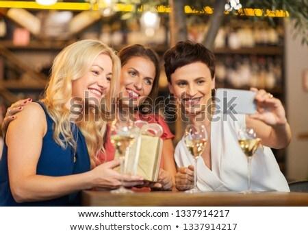 women with gift taking selfie at wine bar stock photo © dolgachov