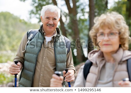 One of mature hikers looking at you while enjoying weekend trip with his wife Stock photo © pressmaster