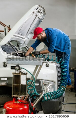 Young technician in workwear bending over open engine of large vehicle Stock photo © pressmaster