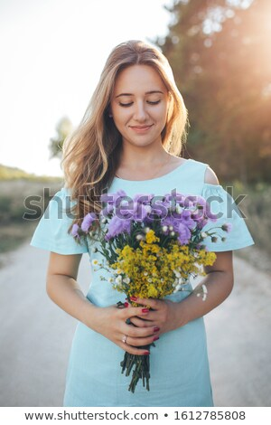 Beautiful young woman outdoors with a bouquet of wild flowers stock photo © lightpoet