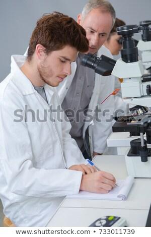Mężczyzna biologii nauczyciel patrząc mikroskopem klasie Zdjęcia stock © HighwayStarz