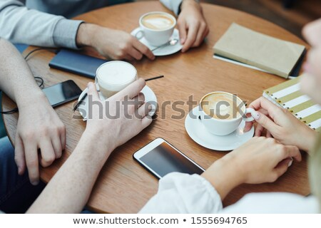 Hands of college friends with gadgets and drinks gathered by table in cafe Stock photo © pressmaster